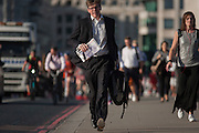 A hurrying businessman with other commuters crosses London Bridge, from the City of London to the south bank of the Thames in Southwark, England UK.