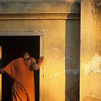 Asia, Laos, Luang Prabang, Young Buddhist monks outside Wat Nong Sikhunmeuang Temple at sunset