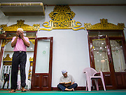 26 JULY 2013 - BANGKOK, THAILAND: Men pray in Haroon Mosque in Bangkok before Iftar. Iftar is the Muslim meal that breaks the day long fast during Ramadan. Ramadan is the ninth month of the Islamic calendar, and the month in which Muslims believe the Quran was revealed. The month is spent by Muslims fasting during the daylight hours from dawn to sunset. Fasting during the month of Ramadan is one of the Five Pillars of Islam. Muslims believe that the Quran was sent down during this month, thus being prepared for gradual revelation by Jibraeel (Gabriel) to the prophet Muhammad.        <br />       PHOTO BY JACK KURTZ