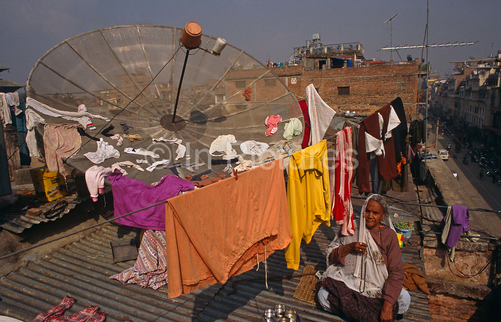 A Nepali lady sits on corrugated iron alongside a giant satellite dish on the roof of her home' in a suburb of Kathmandu, Nepal. We see the sunny street below in the background and other rooftops of scattered aerials, roughly-made brick walls. She has hung her colourful (colorful) clothes washing out to dry on a line and on the structure's bowl-like shape that points towards space and signals from the outside world. It was designed to receive television signals from Nepal's main TV station is Nepal Television (NTV) whose programmes are mostly serials from Pakistan and Hindi films. Nepalis however, search the wider-world for their news digest and western culture, especially during governmental crackdown and censorship during the democracy protest disturbances of 2006. King Gyanendra imposed severe media restrictions after assuming direct control of the country the previous year. The scene is of new technology in the backdrop of a poor, third world country who freedoms of expression and experience of western democracy has been tested in recent years.