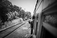 Passengers lean out open doors on a train traveling between the Sri Lankan cities of Colombo and Kandy (April 1, 2017)