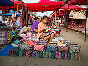 "11 MARCH 2016 - LUANG PRABANG, LAOS:  A vendor sets up her souvenir stand in the handicraft market in Luang Prabang. Luang Prabang was named a UNESCO World Heritage Site in 1995. The move saved the city's colonial architecture but the explosion of mass tourism has taken a toll on the city's soul. According to one recent study, a small plot of land that sold for $8,000 three years ago now goes for $120,000. Many longtime residents are selling their homes and moving to small developments around the city. The old homes are then converted to guesthouses, restaurants and spas. The city is famous for the morning ""tak bat,"" or monks' morning alms rounds. Every morning hundreds of Buddhist monks come out before dawn and walk in a silent procession through the city accepting alms from residents. Now, most of the people presenting alms to the monks are tourists, since so many Lao people have moved outside of the city center. About 50,000 people are thought to live in the Luang Prabang area, the city received more than 530,000 tourists in 2014.      PHOTO BY JACK KURTZ"