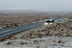 © Licensed to London News Pictures. 03/12/2020. Rhayader, Powys, Wales, UK. A car travels through a wintry landscape on a mountain road  in Elan Valley near Rhayader in Powys, UK. Photo credit: Graham M. Lawrence/LNP