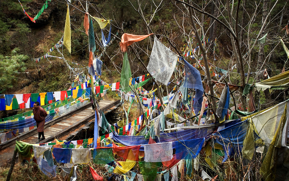 A man walks across a wooden bridge surrounded by prayer flags at Mebar Tsho (burning lake), Bumthang..Commonly described as the last Himalayan Shangrila, Bhutan is a country of unique serenity, harmony, and beauty. Nestled between India, China, and Tibet, this independent country whose name translates as 'the Land of the Thunder Dragon' has for the past 300 years  proactively followed a policy of isolation and cultural protection. Travel in and out of the country is strictly regulated, and the impact of outside influences on the local culture is carefully monitored. Spirituality is an important aspect of Bhutanese culture, with Buddhism being interlinked with everyday life. Gross National Happiness (GNH), as opposed to GNP/GDP, forms the cornerstone of its development strategy which focuses on a holistic development strategy that complements its cultural and Buddhist spiritual values.