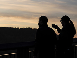 United States, Washington, couple taking cell phone photos at  Snooqualmie Fall (silhouette)