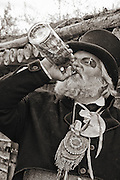 Mountain Man Rendezvous at historic Fort Bridger in southern Wyoming. Photo of a trader drinking from a bottle in his traditional garb.