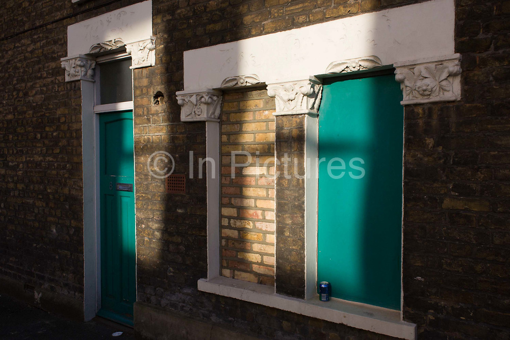A half-bricked up and painted Victorian terraced house window. With the main door to this old period home painted a vibrant green, one half of the window features the same colour while in the middle section, bricks have replaced a pane of glass, in the manner that Georgian property owners doid when faced by government window taxes - penalising those with glass window and a solitary beer can rests on the sill of the right window.
