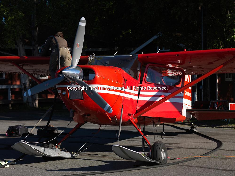 Pilot Chris Wilson fueling K2 Aviation's Cessna 185 on wheel-skis, Talkeetna Airport, Talkeetna, Alaska.