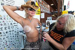 Michelle Maurer of Allentown, PA gets body painted outside The Knuckle Saloon during the 75th Annual Sturgis Black Hills Motorcycle Rally.  SD, USA.  August 2, 2015.  Photography ©2015 Michael Lichter.