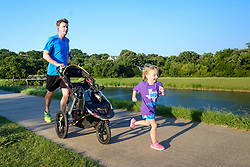 Man and young girl jogging with stroller on Trinity Trails near the Trinity River, Fort Worth, Texas, USA.