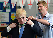 "© Licensed to London News Pictures. 23/04/2013. London, UK Teacher, Ed Wickstead helps Boris Johnson fit the ""sound field"" microphone for the lesson. Mayor of London, Boris Johnson takes part in a Year 6 Class about St George's Day at Tidehall Academy in Deptford, South East London today 23rd April 2013. The class was taught by ""Outstanding Teacher"" Ed Wickstead. During the lesson Mr jOhnson wore a ""sound field"" device around his neck so his voice could be heard by the class. Photo credit : Stephen Simpson/LNP"