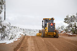 tractor plowing a dirt road in the Winter