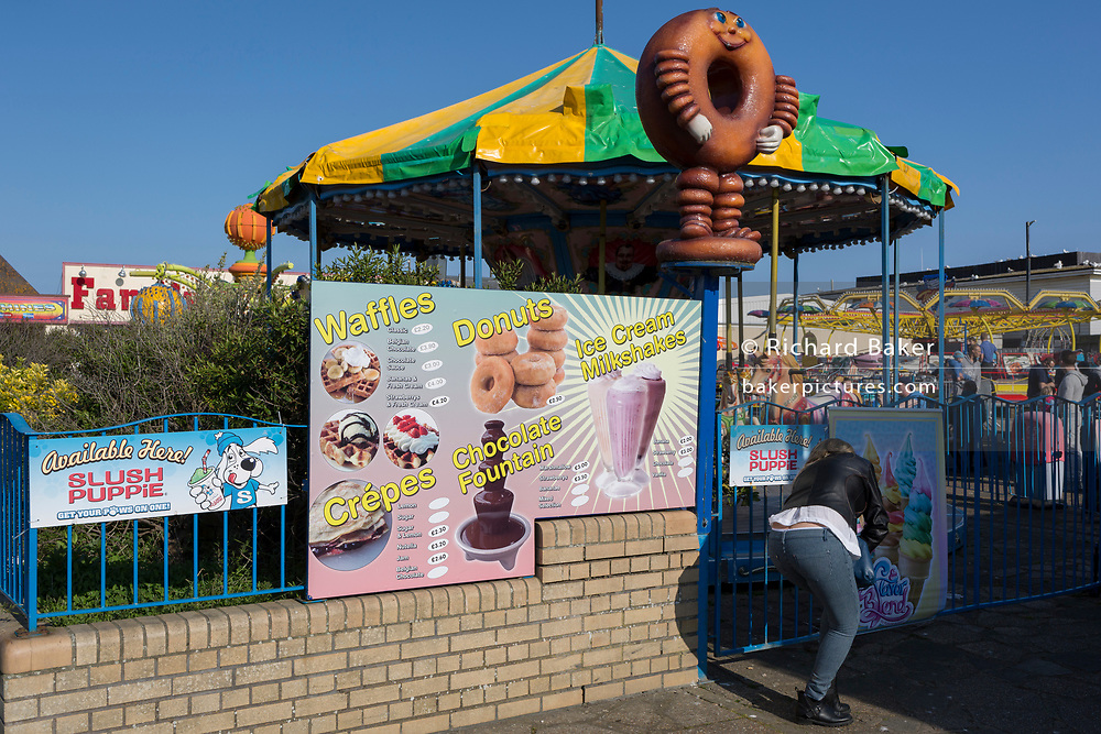 A menu sign advertising poor nutrition of sugary snacks including donuts and waffles near a childrens' fairground, on 29th April 2017, at Hastings, East Sussex, England.