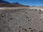 Small rocks litter the desert in the Bolivian Altiplano, surrounded by volcanoes