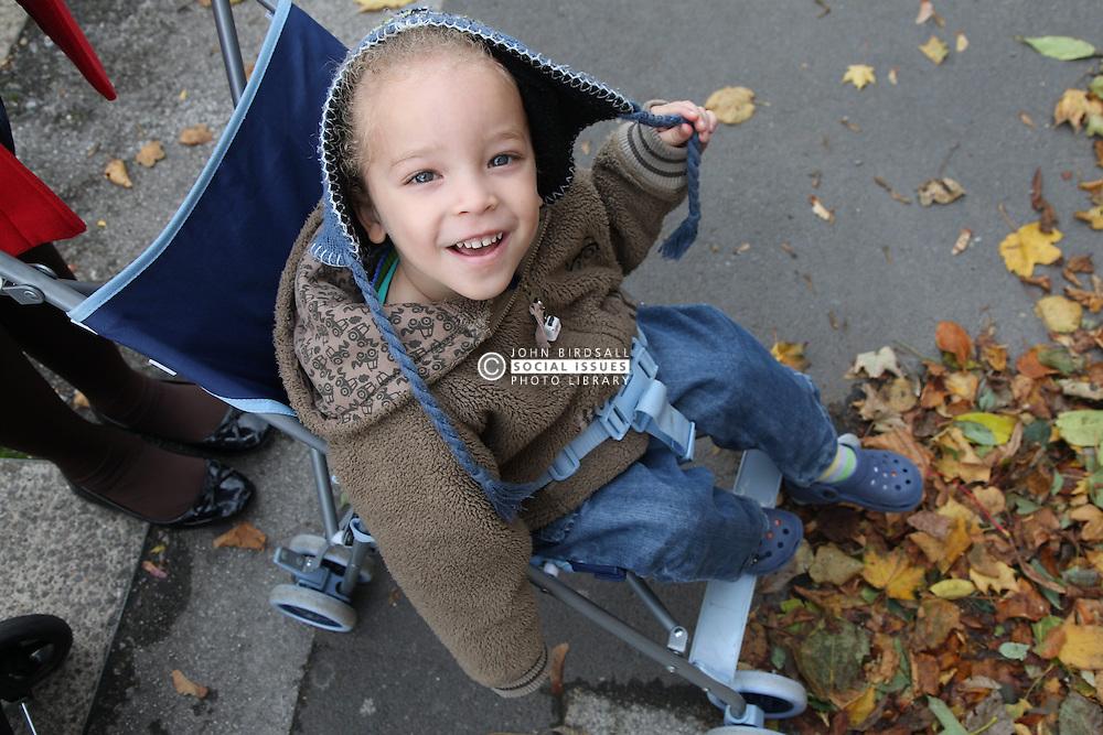 Toddler in coat smiling, dual heritage, boy