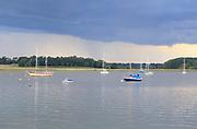 Dark rainclouds River Deben moored boats, Ramsholt, Suffolk, England, UK
