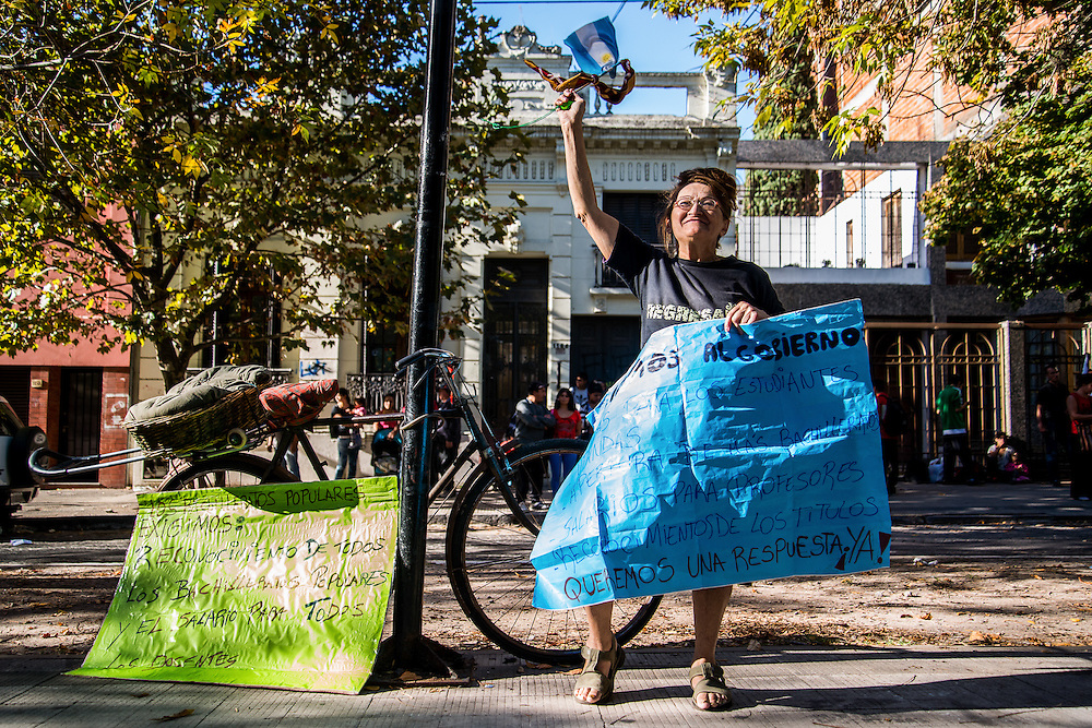 2015, Buenos Aires, Argentina. A woman shows a sign that asks for improvements in public education in front of the Buenos Aires' Education Ministry in La Plata.