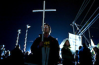 A protester holds up a cross as he protests outside San Quentin Prison, the night before the execution of Stanley Tookie Williams, Monday Dec. 12, 2005.