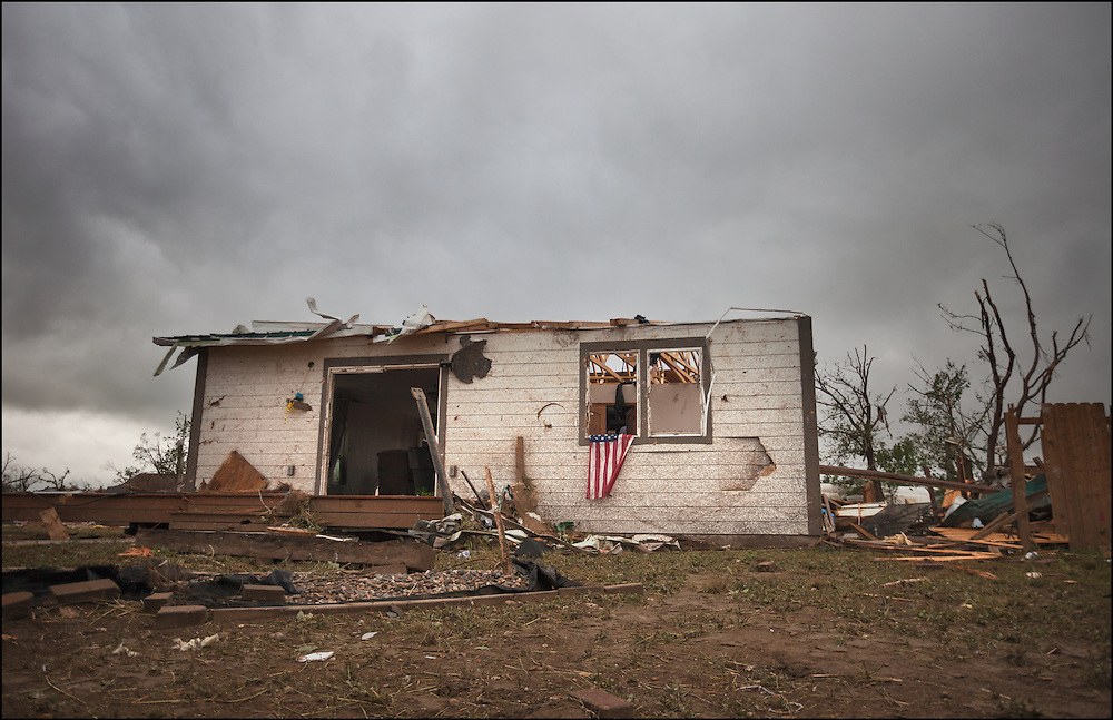 Resident of Baker, Montana hangs an American Flag out of the window of their house that was destroyed by an EF-3 tornado in June 2016.