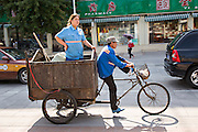 A Chinese woman rides in the back of a trash tricycle during summer in Beijing, China
