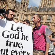 A man tries to drown out the religious protestor. A few Christians opponents of the bill made themselves hear using a speaker and posters. They threatened the crowd with God's ponishment for being sinners. The moment when it is announced that the Same Sex Marriage bill had been passed. London Gay Chorus and supporters of the bill celebrate outside the House of Lords. The campaign for the bill has lasted decades. Summary of the Marriage (Same Sex Couples) Bill 2012-13 to 2013-14<br /> A Bill to make provision for the marriage of same sex couples in England and Wales, about gender change by married persons and civil partners, about consular functions in relation to marriage, for the marriage of armed forces personnel overseas, and for connected purposes.
