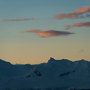 As the sun dips below the horizon it casts orange glows on the clouds above a silhouetted mountain range in Antarctica.