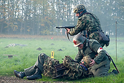 A Re-enactor portrayiing a fallschirmjager gives covering fire as a field medic goes to the aid of a comrade during a battle battle re-enactment in on Pickering Showground<br /> <br /> 17/18 October 2015<br />  Image © Paul David Drabble <br />  www.pauldaviddrabble.co.uk