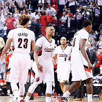 25 April 2016: Portland Trail Blazers guard Damian Lillard (0) reacts next to Portland Trail Blazers guard Allen Crabbe (23) and Portland Trail Blazers forward Al-Farouq Aminu (8) during the Portland Trail Blazers 98-84 victory over the Los Angeles Clippers, during Game Four of the Western Conference Quarterfinals of the NBA Playoffs at the Moda Center, Portland, Oregon, USA.