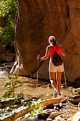 USA Utah, hike up the slot canyon known as Kanarra Creek, near Zion National Park, showing the red iron oxide rocks and the water stream erosion creating magnificent scenery. Model Released MR.