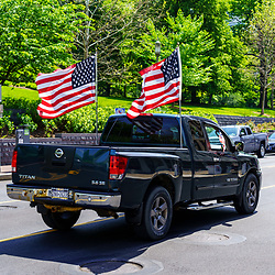 Harrisburg, PA / USA - May 15, 2020: A pick up truck displays two USA flags as it is driven on a city street near the state capitol building.