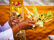 """08 AUGUST 2017 - UBUD, BALI, INDONESIA: A Hindu priest blesses a small basket of offerings during a ceremony to honor a family temple in Ubud, Bali. Balinese Hindus have a 210 day calender and every almost every family compound on Bali has a family temple. Once a year (or every 210 days) families celebrate the """"birthday"""" of their temple with a ceremony.     PHOTO BY JACK KURTZ"""