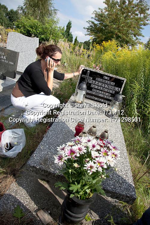 Woman talking on cell phone at mother's grave. Roman Catholic Church's Cemetery Cmentarz Rzymskokatolicki Lodz Central Poland