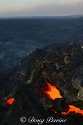 skylights in the roof of a lava tube reveal the red hot liquid lava traveling through the tube toward the ocean from Kilauea Volcano, Hawaii Volcanoes National Park, Ka'u, Hawaii ( the Big Island ), USA