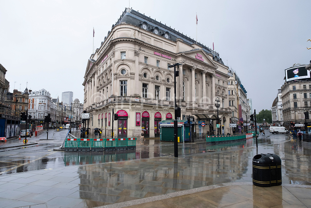 Scenes of a very quiet Piccadilly Circus during a rain shower under coronavirus lockdown on 1st July 2020 in London, England, United Kingdom. As the July deadline approaces and government will relax its lockdown rules further, the central London remains very quiet, while some non-essential shops are allowed to open with individual shops setting up social distancing systems.