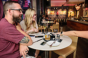 Oscar proposes marriage to Madeline near the sculpture of a Satyr holding an apple that the staff refer to as Randy, Friday, Aug. 14, 2020 at The Bar at Proof on Main in 21c Museum Hotel in Louisville, Ky. (Photo by Brian Bohannon)