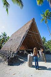 Woman visitors observing a reconstructed old Hawaiian work shed, called Halau, Pu`uhonua o Honaunau or Place of Refuge National Historical Park, Honaunau, Big Island, Hawaii