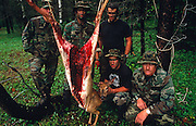 Standing with a recently-killed deer run-over on a nearby highway, members of a special US Air Force (USAF) survival course (see Corbis image 42-18212808) pose by the gutted carcass of their animal in a forest near their facility at Fairchild AFB, Spokane, Washington State. These tough-looking men host visiting air crew whose flying careers depend on passing this rigorous week of escape and evasion instruction. Should they land in enemy territory for example, they will need all the skills learned here to survive possibly weeks in the wilderness so trapping and preparing fresh meat for human consumption is of paramount importance. Here the teachers stand around the venison which is strung up on a branch, its intestines and organs already removed by a hunting knife. They wear camouflage uniforms, face paint to look vicious, threatening and heartless. .