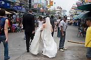 Bride carring the train of her wedding dress and groom rush along Khao San Road, Bangkok. Khao San Rd. is a popular place for tourists to visit with busy bars for the nighttime and shops selling all they require during the day.