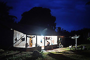 Surui home at night<br /><br />An Amazonian tribal chief Almir Narayamogo, leader of 1350 Surui Indians in Rondônia, near Cacaol, Brazil, with a $100,000 bounty on his head, is fighting for the survival of his people and their forest, and using the world's modern hi-tech tools; computers, smartphones, Google Earth and digital forestry surveillance. So far their fight has been very effective, leading to a most promising and novel result. In 2013, Almir Narayamogo, led his people to be the first and unique indigenous tribe in the world to manage their own REDD+ carbon project and sell carbon credits to the industrial world. By marketing the CO2 capacity of 250 000 hectares of their virgin forest, the forty year old Surui, has ensured the preservation, as well as a future of his community. <br /><br />In 2009, the four clans and 25 Surui villages voted in favour of a total moratorium on logging and the carbon credits project. <br /><br />They still face deforestation problems, such as illegal logging, and gold mining which causes pollution of their river systems