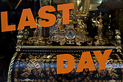 Last day of trading of a Knightsbridge shop selling period furniture in central London. The lettering stretches across the window behind which we see ornate antiques from unknown periods of history. A carriage clock occupies prime site on a writing desk with elaborate illustration and gold leaf decoration. A chandelier is also in the background with statuettes and other fixtures for the period home.