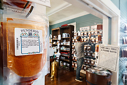 Packages of Scorpion Trinidad Moruga Chile powder at Pendery's World of Chiles & Spices Fort Worth store, with shopper in background, Fort Worth, Texas USA. It is one of the world's hottest and most sought after chiles.