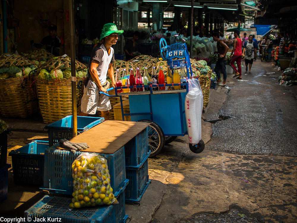 01 APRIL 2014 - BANGKOK, THAILAND: A snack vendor pushes his cart through the flower market in Bangkok. The Yodpiman Flower Market (also called Pak Khlong Talat) is being renovated and gentrified. The market opened in 1961 and has been a Bangkok landmark for more than 50 years, is being turned into a high end mall. Many of the flower and vegetable vendors in the market may be forced out.    PHOTO BY JACK KURTZ