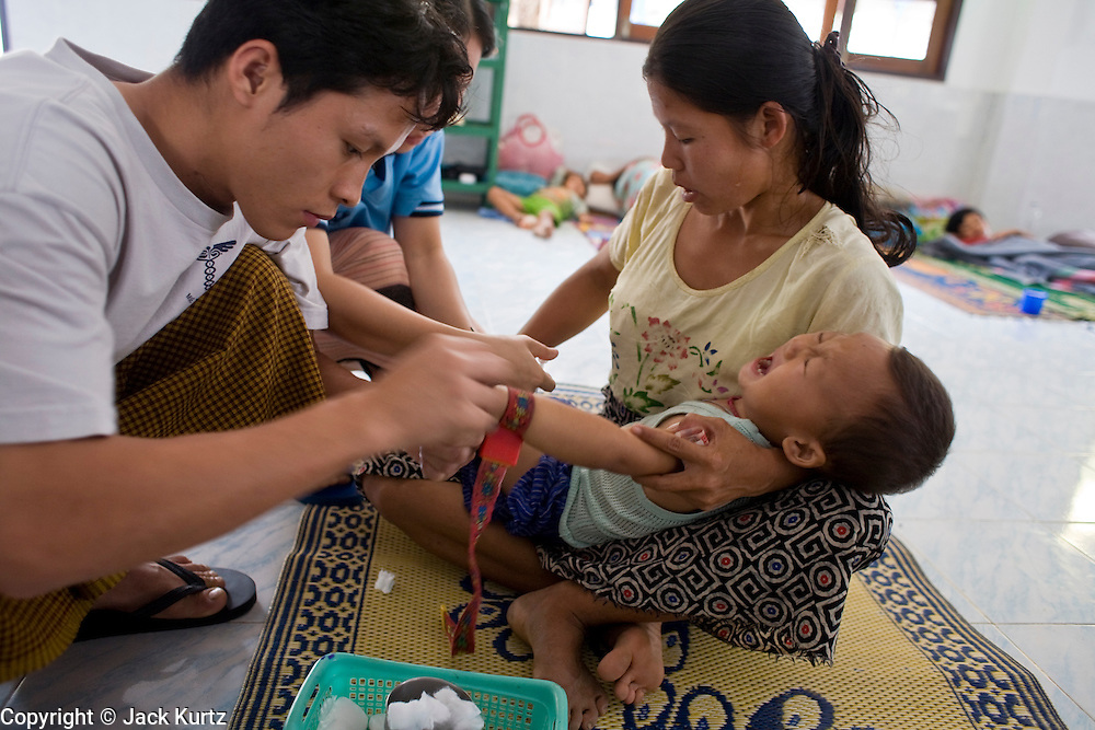"""23 FEBRUARY 2008 -- MAE SOT, TAK, THAILAND: Clinic workers try to start an IV in Ti Su Wa, a 2 year old Karen boy at the Mae Tao Clinic in Mae Sot, Thailand. His mother said he had been sick for more than a week but that she couldn't afford medical care in Burma so she crossed illegally to Thailand to get treatment at the clinic. The clinic treated more than 80,000 people in 2007, all Burmese. Most of them are living illegally in Thailand, but many come to the clinic from Burma because they either can't afford medical care in Burma or because it isn't available to them. There are millions of Burmese refugees living in Thailand. Many live in refugee camps along the Thai-Burma (Myanmar) border, but most live in Thailand as illegal immigrants. They don't have papers and can not live, work or travel in Thailand but they do so """"under the radar"""" by either avoiding Thai officials or paying bribes to stay in the country. Most have fled political persecution in Burma but many are simply in search of a better life and greater economic opportunity.  Photo by Jack Kurtz"""
