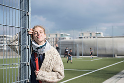 Young woman leaning on metal fence with eyes closed, Munich, Bavaria, Germany