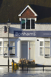 © Licensed to London News Pictures. 03/01/2014. Guildford, UK Bonhams uses sandbags to stem the floodwater. Guilford town centre River Wey bursting it's banks in Surrey today 3rd January 2013. Floods an heavy rain are continuing to effect travel and people across the country today. Photo credit : Stephen Simpson/LNP