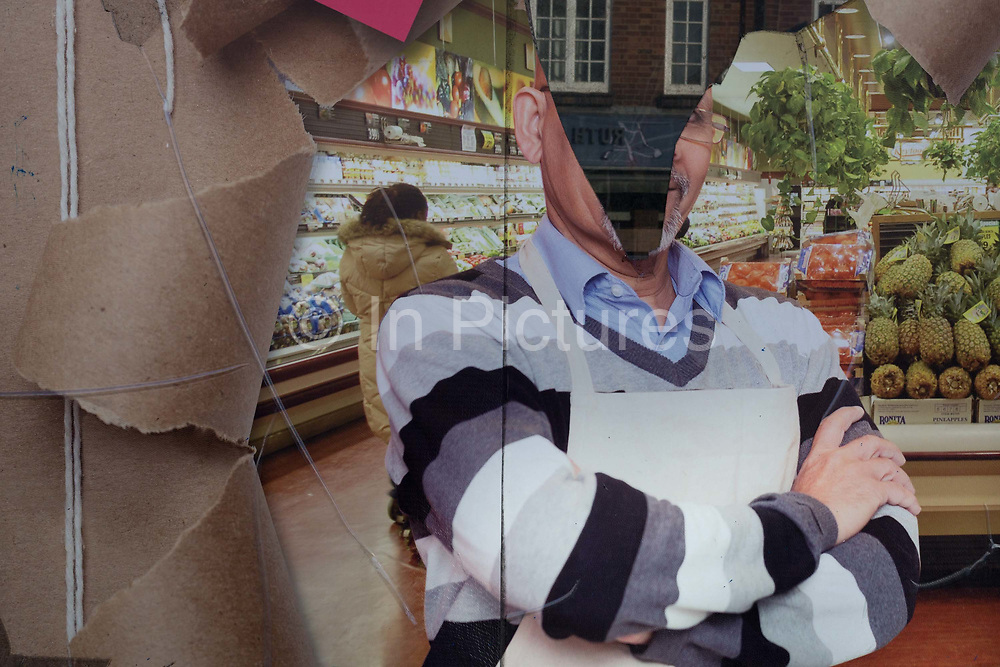 A detail of a torn shop poster showing a supermarket manager, in the window of a business in Orpington High Street, on 5th February 2020, in London, England. A near-perfect V has been ripped across the mans head to create a confusing and ambiguous graphic perspective.