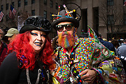 New York, NY - 21 April 2019. A woman with bright red hair and a black hat trimmed with black flowers next to a man with a hat bristling with artist's paintbrushes at the Easter Bonnet Parade and Festival on New York's Fifth Avenue.