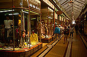 An original Victorian shopping arcade in the seaside resort town of Great Yarmouth on the English east coast. Daylight floods in through overhead skylight roof glass  as shoppers walk past local ladies fashion displays seen behind beautiful curved windows, in the style of late 19th century. Tiles flooring acts as a pavement to resembled an upper-class covered street to keep visitors dry from frequent coastal showers. The shops are local too - without branded chains occupying the site and forcing hardship on local businesses.