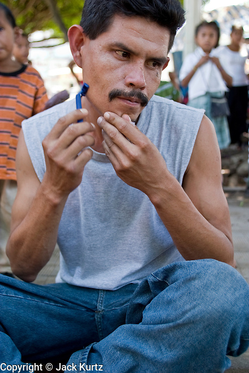 26 JULY 2004 -- TAPACHULA, CHIAPAS, MEXICO:  A man in Tecun Uman, Guatemala, on the Rio Suchiate, which is the border between Mexico and Guatemala, shaves while he waits to enter Mexico illegally on their way to the US. They plan to catch a freight train in Tapachula to ride north to Mexico City. Tapachula is center of the smuggling industry between Mexico and Guatemala. Consumer goods are smuggled south to Guatemala (to avoid paying Guatemalan import duties) and people are smuggled north into Mexico. Most of the people coming north are hoping to eventually get to the United States.PHOTO BY JACK KURTZ