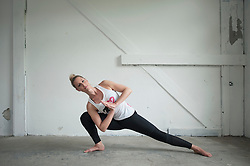 Mid adult woman practicing parighasana pose in yoga studio, Munich, Bavaria, Germany